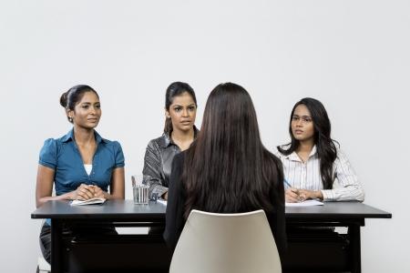entrevista: Tres colegas indios departamento de recursos humanos de entrevistar a un solicitante femenino joven. Foto de archivo