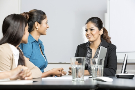 Happy Indian business woman sitting with her colleagues in a meeting photo