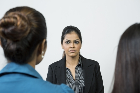 Indian colleagues having a meeting or interviewing a female applicant photo