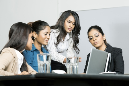 indian chief: Indian female business colleagues working around a laptop Stock Photo
