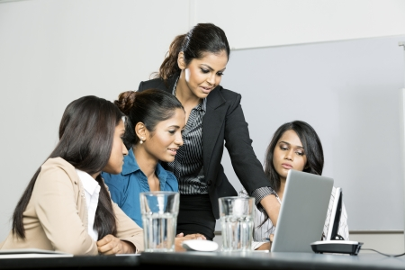 Indian women business colleagues working around a laptop photo