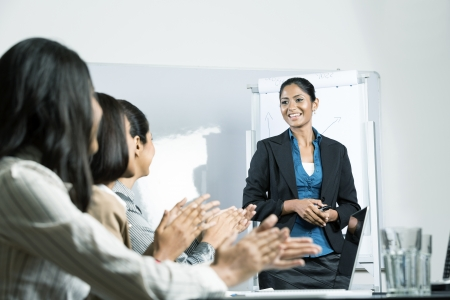 business woman standing: Successful Indian business woman standing by whiteboard while her colleagues are clapping her.