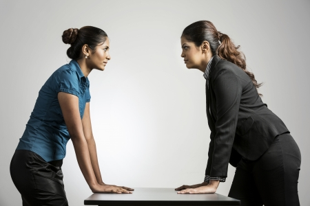 standoff: Indian business women staring at each other.  Two business rivals having a standoff.