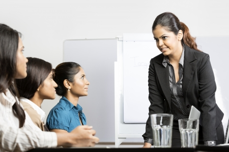 bad plan: Serious boss talking with her team during a meeting. Indian business woman. Stock Photo