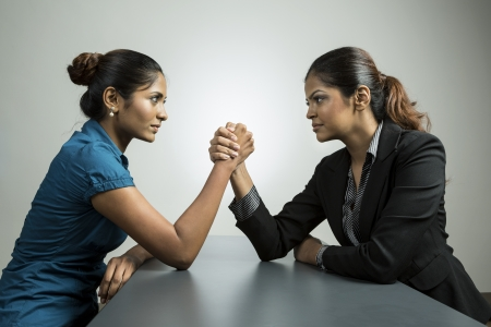 competing: Two Indian business women having an arm wrestle challenge. Conceptual business image about power and control.