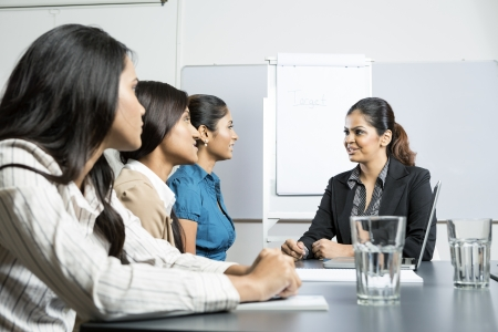 Indian business woman sitting talking with her colleagues in a meeting photo