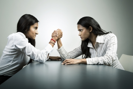 assertive: Two colleagues aggressively arm wrestle. Conceptual business image about power and control. Stock Photo