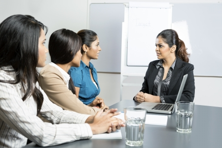 indian girl: Indian business woman talking with her team during a meeting.