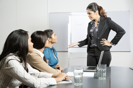 mujer enojada: Angry jefe hablando con su personal durante una reunión. Mujer de negocios indio.