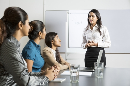 Indian woman at a business meeting, giving a presentation. photo