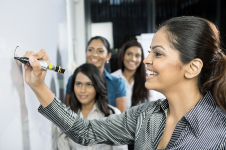 Indian Business women discussing ideas and writing them on whiteboard. Stock Photo - 16771859
