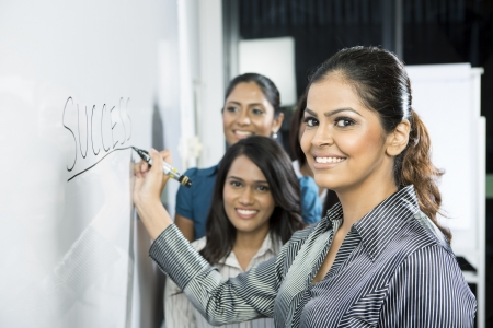 Indian business woman writing success on a whiteboard with her team around her. photo