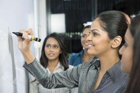 Mujer de negocios indio escribiendo en una pizarra con su equipo a su alrededor. Foto de archivo