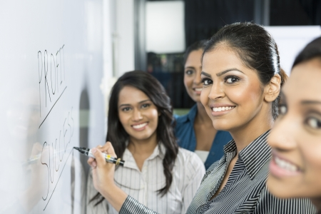 whiteboard: Indian business woman writing success on a whiteboard with her team around her.