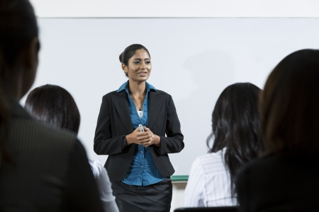 Indian business woman giving a presentation in front of an audience. photo