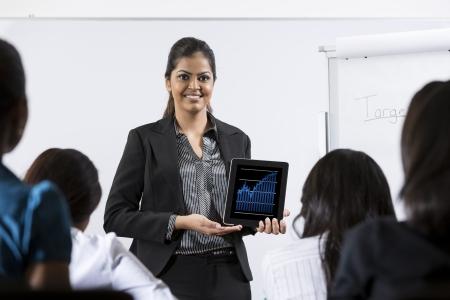 Indian Geschäftsfrau diskutieren Finanzen Diagramm auf einem Touch-Pad.