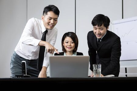 Chinese business team working together around a laptop photo