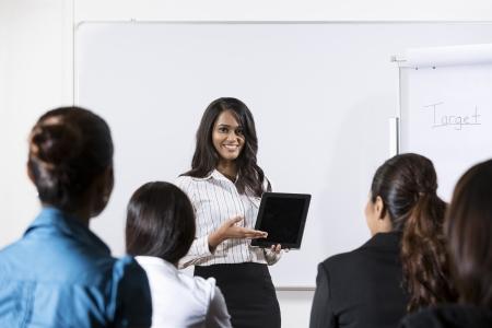 Indian Geschäftsfrau diskutieren Informationen auf einem Tablet PC angezeigt