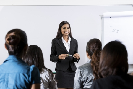 Indian business woman giving a presentation in front of an audience.