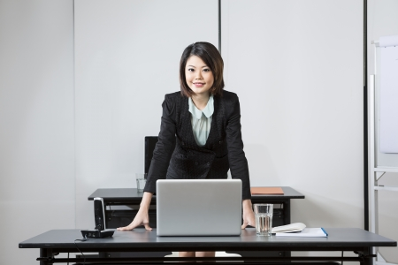 Attractive Chinese Business Woman leaning on her desk. photo