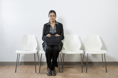 restless: Smart Indian business woman waiting for a job interview. Sitting on a row of chairs