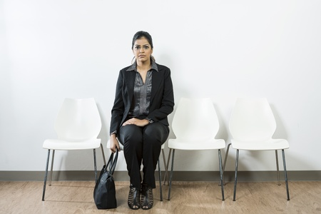 check room: Anxious Indian woman waiting for a job interview while sitting on a row of chairs