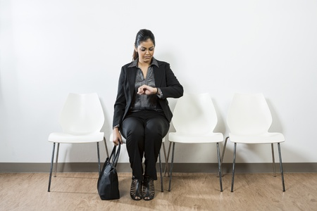 check room: Indian business woman waiting for a job interview and checking the time. Stock Photo