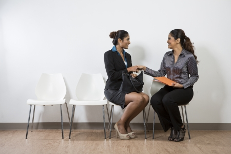 business interview: Happy Indian business women shaking hands at a job interview or meeting.