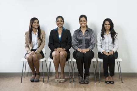 Happy and smiling Indian business team sitting in a row at office. photo