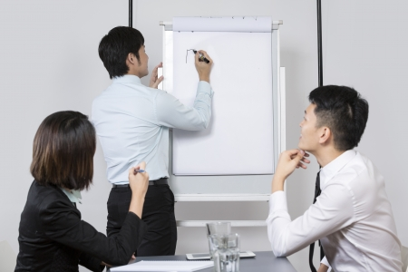 Chinese Business team discussing ideas and writing them on whiteboard. Stock Photo