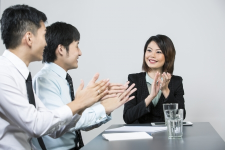 congratulating: Successful Chinese business woman clapping and congratulating her colleagues.