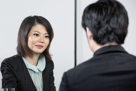 Chinese man having an interview with female manager. photo