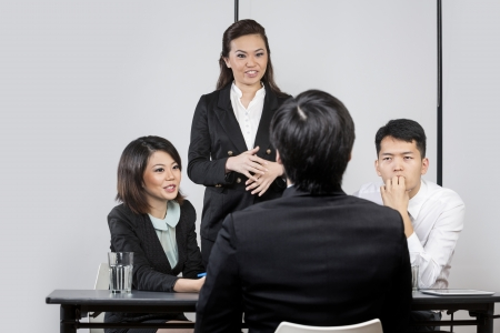 Panel of Chinese colleagues from hr department interview a male applicant. photo