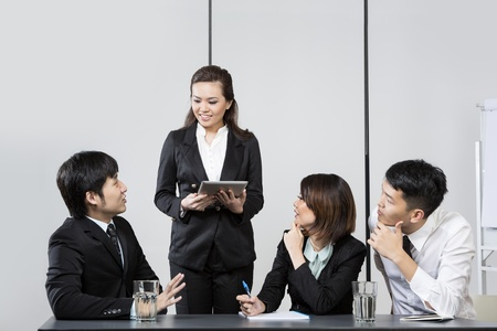 briefing: Chinese Business woman leading a meeting in the office. Stock Photo