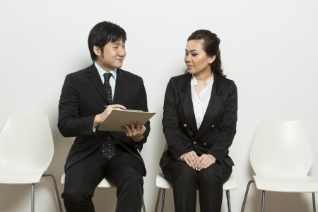 applicant: Happy Chinese business man interviewing female applicant.