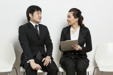 applicant: Chinese business woman interviewing an uncomfortable looking male applicant. Stock Photo