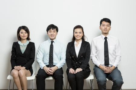 south asian: Happy Chinese business team sitting in a row at office.
