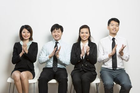 Successful Chinese business team sitting in a row and clapping. photo