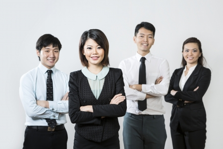 professionals: Chinese business woman with her team out of focus behind her.