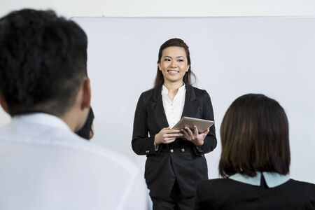 Chinese Business woman giving presentation with a Digital Tablet photo
