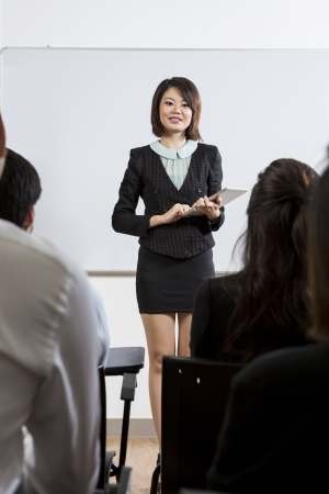 Chinese Business woman discussing information shown on a Digital Tablet Stock Photo - 16771762