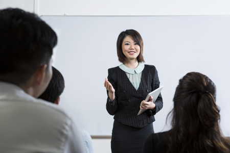Chinese Business woman giving presentation and holding a Digital Tablet photo