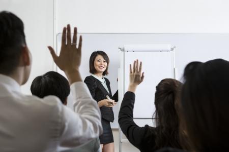 formacion empresarial: La gente de negocios Raising hay mano para arriba en una Conferencia para responder a una pregunta Foto de archivo