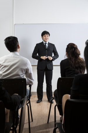 Happy looking Chinese Business man giving presentation photo