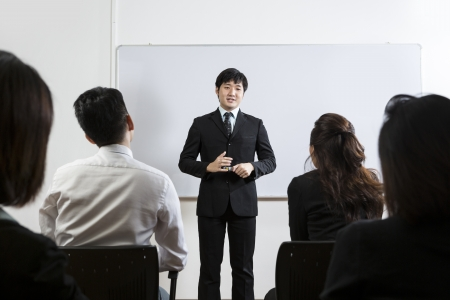 staff meeting: Happy looking Chinese Business man giving presentation Stock Photo