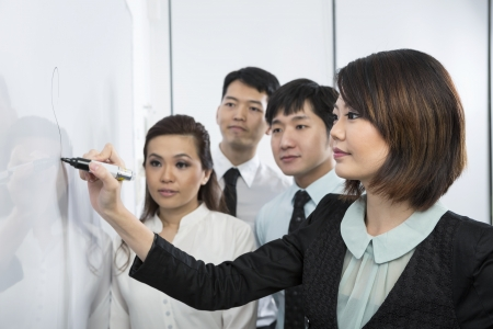 training group: Chinese business woman writing on a whiteboard. Her team are behind her out-of-focus.