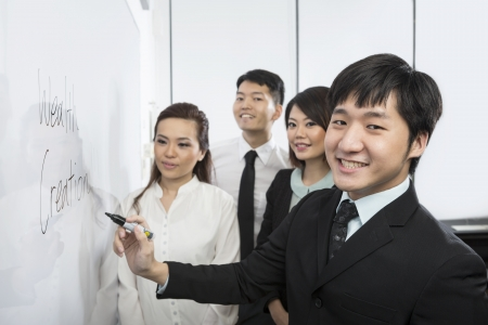 Chinese business man writing on a whiteboard with his team around him. Stock Photo
