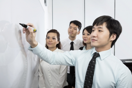 briefing: Chinese business man writing on a whiteboard with his team around him. Stock Photo