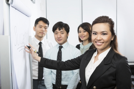 Chinese business woman writing Success on a Flip Chart with her team around her. photo