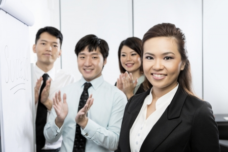 Successful Chinese business woman with her team clapping and congratulating her. photo